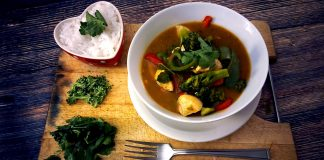 Served on a board is a bowl of red Thai chicken curry with a heart shaped side dish of Thai Jasmine rice