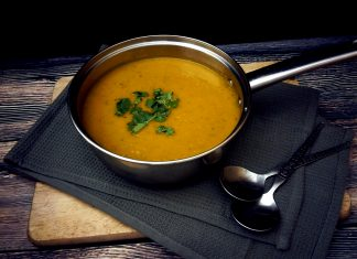 A pot of carrot and coriander soup with fresh chopped coriander sprinkled on top set at the dinner table, ready to tuck into.