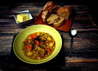 A big bowl of homemade Irish stew served with a loaf of freshly made soda and some butter on the side