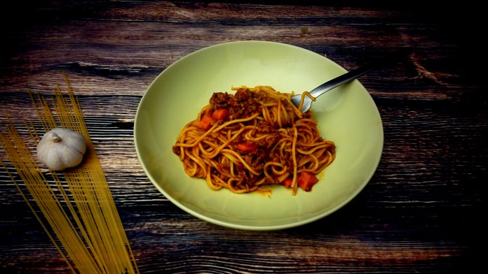 A large bowl of spaghetti with a rich tomato bolognese sauce to accompany it. A perfect bowl of spaghetti bolognese.