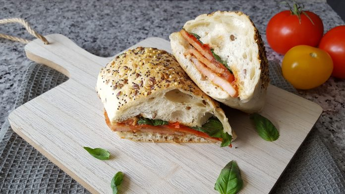 Panini sliced in half with bacon, fresh tomatoes and basil presented on a wooden board with fresh tomatoes in the background for decoration.