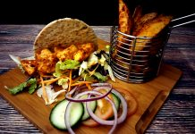 Chunks of chicken served on a flatbread with lettuce leave, sliced carrot, tomato, red onion and cucumber with a dollop of garlic sauce. A basked of home cooked fries on the side.