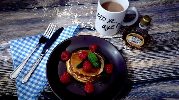 Protein pancakes served on a plate with fresh raspberries, mint leaves and a drizzle of Canadian maple syrup. Served with a mug of tea and the slogan 'Did ye aye?'