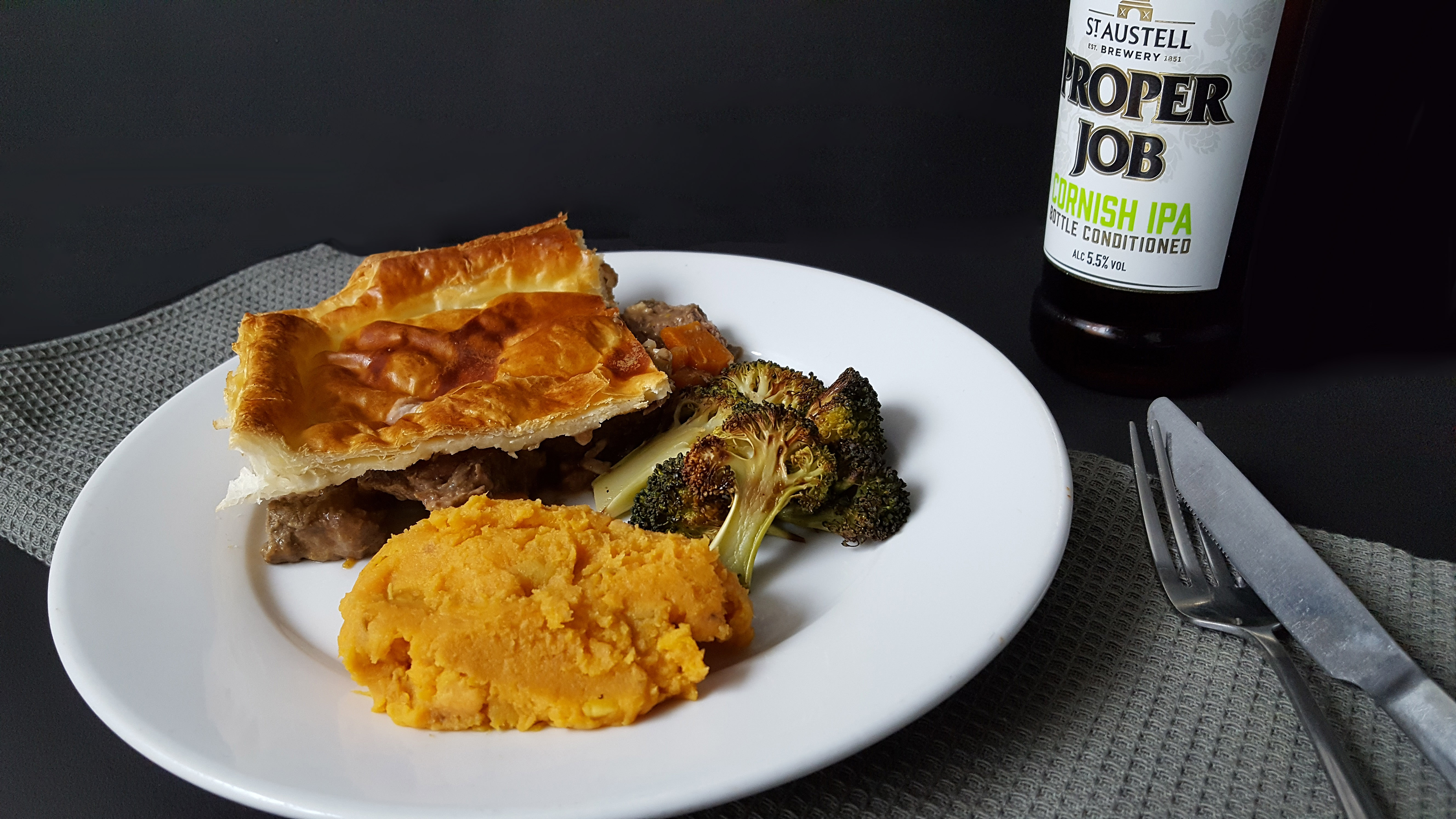 Steak Pie served on a plate with flaky puff pastry on top along with sweet potato mash and roasted broccoli. Plus a bottler of Proper Job pale ale.